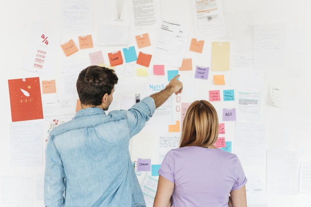 young-employees-looking-wall-with-marketing-notes_23-2148222645